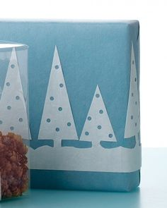 """Wintry Scene Cutout for Gift Wrap. Create a wintry scene on a wrapped present using a paper-dolls technique. Enlarge the two-tree template to desired size; cut out. Accordion-fold a piece of paper to the width of the template. Trace the template onto top fold. Make """"ornaments"""" with a screw punch. Cut out and unfurl trees. Adhere with a glue stick or spray adhesive."""