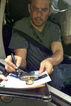Paul Walker signing a picture during a break from filming of Brick Mansions.