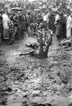 Woodstock concert goers sliding down a muddy hill, 1969