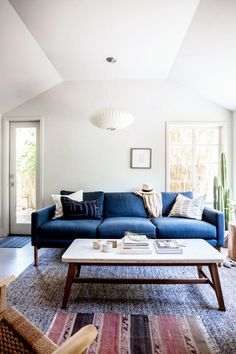 Bohemian inspired living space with a blue sofa, textured area rug, and an indoor cactus