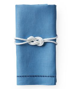 Give napkins at your table settings aGilligan-inspiredtouch. Double up a length of cord (mjtrim.com), hold it in the middle, and tie an 8-knot. Place knot on a folded napkin; wrap ends around. Trim and secure with white gaffer's tape.   Watch Our 8-Knot How-To Video