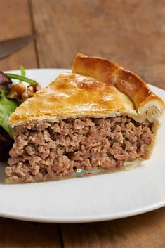 slice of tourtiere on a white plate with knife and whole tourtiere in the background, authentic tourtiere recipe