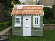 Pretty Playhouse with cedar roof, curtains and window boxes.