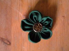green brooch with golden button