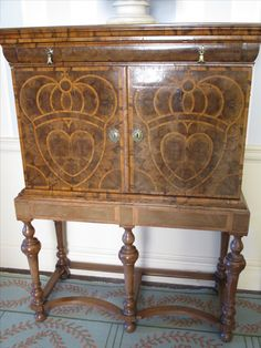 William and Mary walnut oysterwood cabinet on a stand with luckenbooth symbol, and often described as the 'Douglas heart'.   Gained popularity during the reign of Mary Queen of Scots.  First sold from locked booths on the Royal Mile, Edinburgh, a luckenbooth was given as a token of love or betrothal.  This is the oldest piece of furniture at Culzean (17th century) and reflects the family's pride in their ancestor, Robert the Bruce.