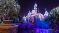 "Sleeping Beauty Castle, a stop on the ""Holiday Time at Disneyland"" Tour, shimmers at night with seasonal lights"