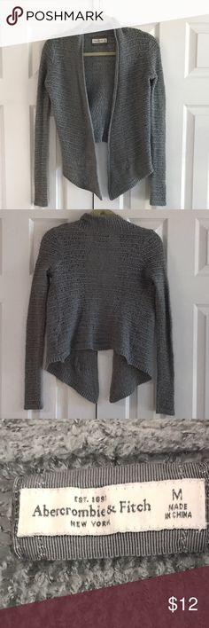 Abercrombie and Fitch cardigan 43% acrylic 30% nylon 27% wool hand wash cold. It regular size gaps throughout entire knitted sweater. Color is a medium gray. Front angles into a point.  Armpit to armpit across the back is about 17 inches. Shoulder to bottom him in the back is 19 inches. It hangs lower in the front since it is angled. No rips no stains.   Small A&E plaque on the bottom left side. Photo 4. Abercrombie & Fitch Sweaters Cardigans