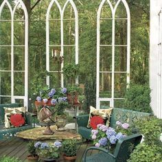 Old church windows (flea market finds) hung from rails set atop corner posts enclose a 16-by-16-foot deck, giving it the elegant air of a glass-lined conservatory. | Photo: Van Chaplin | thisoldhouse.com