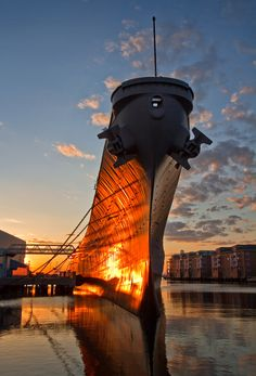 USS Wisconsin - Battleship USS Wisconsin (BB-64), an Iowa class battleship, one of the largest battleships ever build by the U.S. Navy, now berthed at Nauticus in Norfolk, Virginia. Here the last rays of the setting sun light up her sides with a coppery glow.