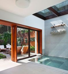A high skylight gently illumines a tranquil semi-indoor therapeutic pool.