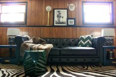 The Jungle Room Den Makeover inspired by Elvis' Jungle Room: They kept the paneling and it actually looks really good with the black trim!   Zebra Print Rug   Malachite Side Table   Black Leather Chesterfield couch