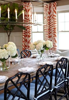 The natural wood table's rustic charm is enhanced by the smooth, clean lines of the glassware. The table has two centerpieces with white hydrangeas neatly arranged.