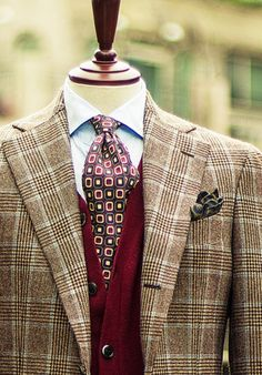 A plaid wool coat over a red vest and patterned necktie.
