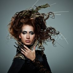 Stock image of 'High fashion model in black dress, with long nails and creative hairstyling on grey background'