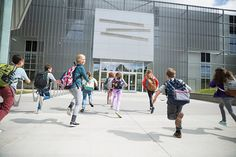 Enthusiastic school kids running toward science center entrance