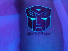Autobot black light tattoo on the leg Uv Tattoo, Best Tattoo Ink, Real Tattoo, Dark Tattoo, First Tattoo, Cool Tattoos, Geek Tattoos, Small Japanese Tattoo, Japanese Tattoos