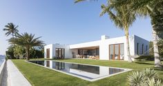 White modern beach house with pool and green lawn