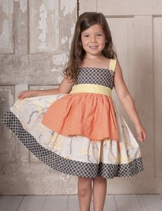 OMG! This new brand is playfully brilliant with their mix of colors and fabric choices! This new brand Binx Kids brand is manufactured and family owned in the US. These pieces are made of 100% cotton and are beautifully layered and designed for a unique look. This precious apron dress has a lattice print bodice with a yellow print sash that sweetly ties in the back. The apron is a spring peach color that complements the other patterns and colors. This precious dress buttons up the back…