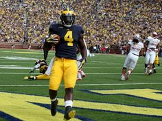 Michigan running back #4 De'Veon Smith celebrates in the end zone after scoring Michigan's first touchdown making the score 7-0 in the first quarter of the game between the University of Michigan vs the University of Las Vegas Nevada at Michigan Stadium in Ann Arbor, Michigan on Saturday, September 19, 2015.