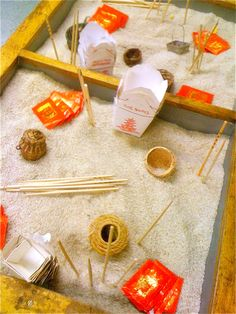 Chinese New Year sensory table: rice, chopsticks, take out containers, red envelopes, small baskets