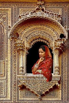 Indian lady looking out of a Jharokha (ornate window)