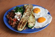 Eggs, pan-fried zucchini with chili, salt and pepper; quinoa in tomato sauce with chopped black olives, tomato and parsley, topped with feta cheese and more parsley