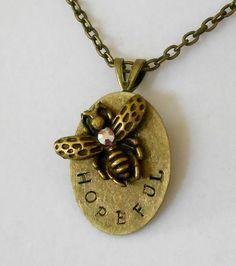 It is an antiqued brass finish hand stamped oval pendant, with a antiqued brass bee attached with a genuine Swarovski aurora borealis crystal accent on its back. It is a cute play on words.     There is the Bee, and then... the word of choice.     Choose from :     Nice   Kind   Hopeful   Strong   The Change   Logical     OR choose your own! It has to be under 10 letters including spaces.