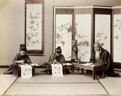 Children learning calligraphy from master calligrapher, hanging scroll and folding screen with decorative painting in background, ca. 1890