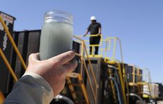 A jar holding waste water from hydraulic fracturing is held up to the light at a recycling site in Midland, Texas, Sept. 24, 2013. With fres...