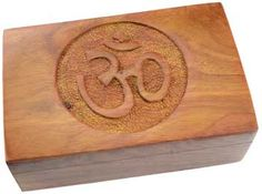 Om Wooden Carved Box | Decorated with an Om Symbol, this wooden box is further sculpted with an elaborate pattern of flowers. Place it in your bedroom, upon your altar, or your desk to store incense, jewelry, ritual tools and more.