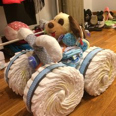 Diaper Four-Wheeler Cake. Used 92 (Size 2) Diapers-wheels. Ribbon as well Various sized rubber bands-Keeps them together 3 pairs of socks (0-3 mo)-handlebars and hub caps Tissue paper for socks. 4 receiving blankets. Bibs One bottle.- headlight Washcloths.
