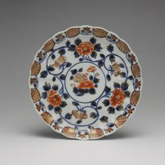 Circular dish of porcelain, decorated in underglaze blue and overglaze enamels with camellia in centre surrounded by scrolling peonies, Imari ware: Japan, c. 1740, K.2005.555