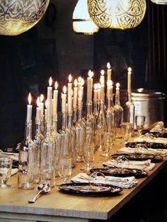 Get this look - clear bottles (you can use left over wine bottles) and long white candles, use a bit of hot glue to keep the candles in place. Vary the lengths of the candles and the types of bottles! Line them up along the length of the table to get this awesome look! #DIY
