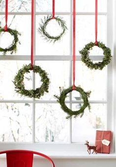 Wreaths aren't just for front doors. How simple is this idea: Using red ribbon, hang a few fresh wreaths at different lengths in front o...