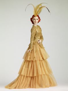"""Tonner's """"Romantic Gold"""" has red rooted hair, green eyes with lashes on a cameo skin tone body. She is dressed in a gold gown with a sequined bodice and tiered ruffled skirt. Her accessories include a gold braided belt, feathered hair decoration, and gold shoes with rhinestone buckle. She's limited to 300."""