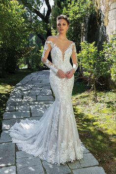 Fall in love with this off the shoulder fit and flare gown. Venice lace adorns the illusion plunging neckline and continues throughout the gown. Tulle covered buttons adorn the back.