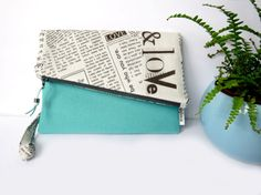 This asymmetrical fold over clutch bag features an inspiring newsprint pattern with aqua blue linen . Both the zipper and magnetic snap will work together to keep your belongings secure while the detachable wrist strap allows you to carry this as a stylish clutch or as a wristlet bag. Inside youll find the bonus factor of a slot pocket which is perfect for storing your phone or keys.  The perfect bag for keeping all of your essentials close at hand while out on-the-go. As this print had so…