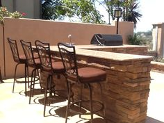 Large custom BBQ with stone veneer and eating area with granite top by Tuscany Builders