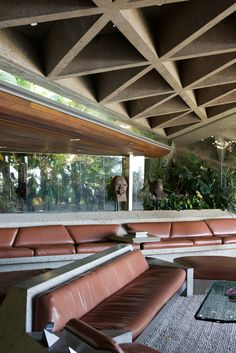 The famous living room is filled with custom leather-and-concrete sofas and geometric concrete ceilings.