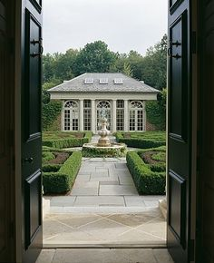 View through double doors out to a hedge garden and a brick Georgian garden pavillion with Palladian windows.