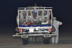 Staff of the emergency medical services, dressed in protection suits, transport a stretcher with the Italian doctor who contracted Ebola while working in Sierra Leone, as he arrives at the Pratica di Mare military airport in Rome, November 25, 2014. The Italian doctor has been flown to Italy to be treated in the Lazzaro Spallanzani infectious diseases institute in Rome. Part 1 of 2