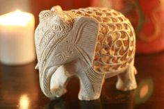 """Mother Elephant :Natural Soapstone Sculpture Carved by Hand  Ruffled rosettes crown an elephant who wears the jingling harness of the royal stables. Carved in dainty jali, or openwork, her tummy reveals two perfect miniature elephants inside.   Product Code : AF-05  Size: 5"""" H x 6"""" W x 3.9"""" D  Weight: 3.5 lbs"""