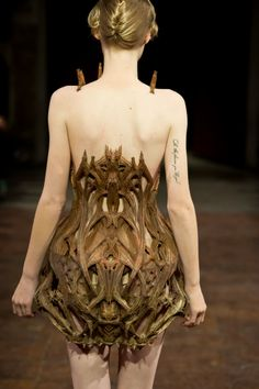 Back of the coolest architectural dress i've ever seen! i love how it's just hanging on her shoulders like a spider that's on her chest.