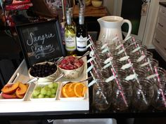 Baby shower sangria station with grey and pink paper straws and cloud name tags.
