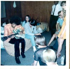 Jimi Hendrix playing guitar, being watched by Peter Tork and Michael Nesmith of The Monkees, 1967