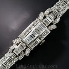 Over 10 carats of icy-white brilliance covers this blindingly beautiful late-Art Deco cover watch, hand fabricated in platinum, circa 1930s. The cover glistens with triple tapered rows of seamlessly-set baguette diamonds that continue straight through to the shoulder links.The bracelet sections feature a center row of straight baguette diamonds bordered on each side by sparkling round brilliant-cut diamonds. A simple flick opens the cover to reveal the Hamilton timepiece. This truly…