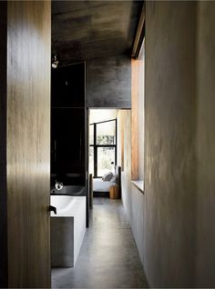 Dulux Ferrodor 810 industrial paint in Mid Grey, dark formply timber ceiling cladding, and concrete floors give the interiors a brooding intensity.
