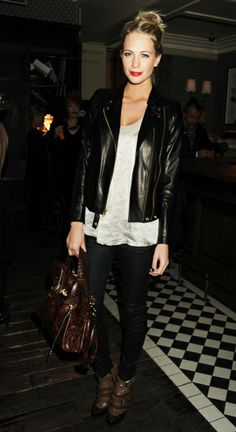 poppy delevigne rocking the typical model uniform. Black leather jacket over a white top paired with black pants. Model street style, models off duty. Blonde hair and red lips.