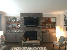 Our beautiful reclaimed wood floating shelves. Flanking stone fireplace with grey base cabinets located in family room. Fireplace Built Ins, Fireplace Shelves, Home Fireplace, Fireplace Remodel, Fireplace Design, Basement Fireplace, Farmhouse Fireplace, Wood Shelves, Propane Fireplace