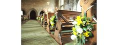 End of church pew yellow and white flowers (daffodils). Photo by Tamsyn Hayward Photography